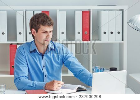 Young Male Businessman Make Notes Looking At Laptop Sitting At Office. Business, Exchange Market, Jo