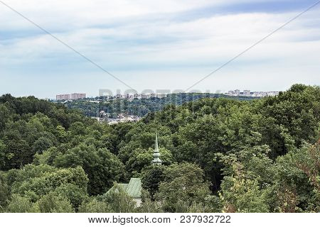 Cityscape Of Lviv, Ukraine. Spire Of Church Is Seen Among Green Trees