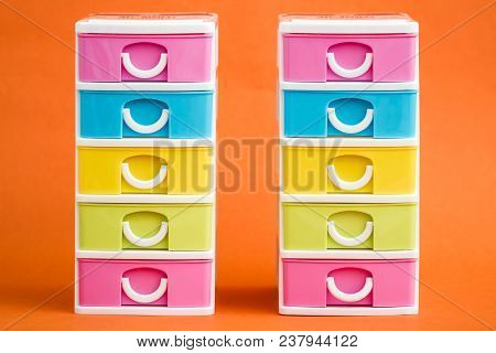 Small, Cute And Colorful Plastic Drawers On Orange