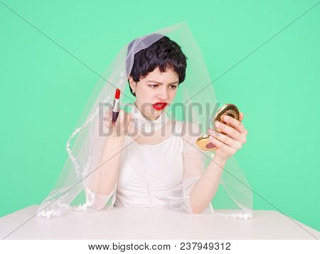 Young enraged bride teenager looking at her hairstyle in a Mirror sitting at table isolated on light background poster