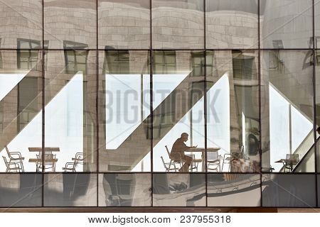 Denver, Usa - November 04, 2016: An Unidentified Man Sits By A Table Looking At His Mobile Phone In