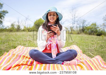 Attractive Smiling Young Woman Dressed Casually Uses E-book/tablet Sitting On A Colourful Blanket In