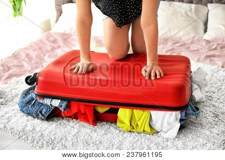 Young Woman Struggling To Close Suitcase On Bed