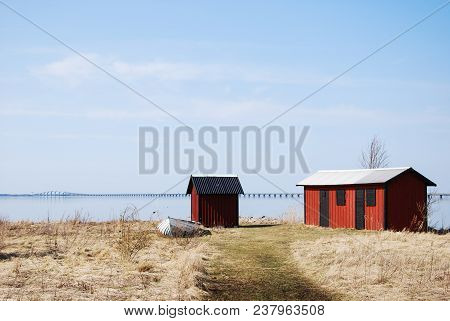 Fishermens Old Red Cabins In Front Of The Landmark The Oland Bridge Crossing A Strait In The Baltic