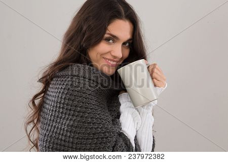 Side View Image Of Alluring Brunette In Gray Cardigan. Holding Cup Of Coffee. Mid Age Woman Over 35