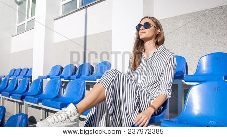 Sexy Stylish Woman In Sunglasses Sitting On Empty Stadium Seats In Bright Sunny Day