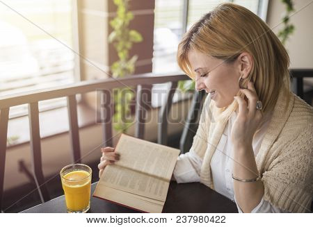 Young Smiling Blonde Woman With Glasses In A Restaurant Reading A Book And Drinking Juice. Relaxing