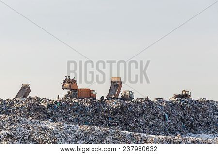 Dump Trucks Unloading Garbage Over Vast Landfill.  Environmental Pollution. Outdated Method Of Wasat