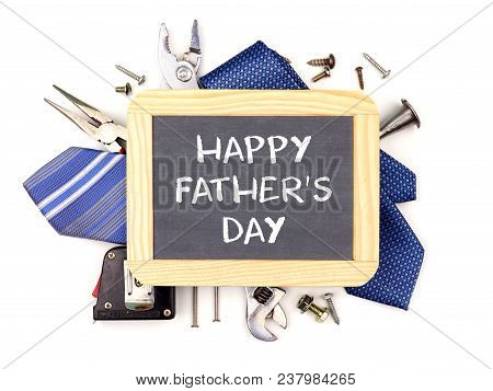 Happy Fathers Day Message On A Chalkboard With Underlying Frame Of Tools And Ties Isolated On A Whit
