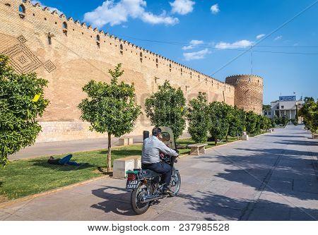 Shiraz, Iran - October 23, 2016: Iranian Man Drives Motorcycle Next To Karim Khan Citadel In Shiraz