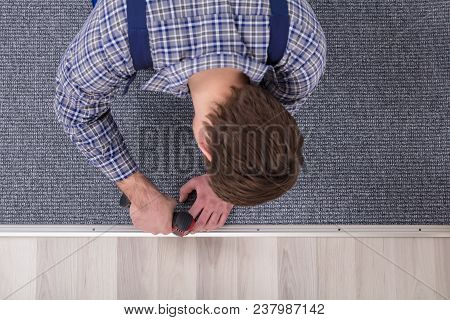 Close-up Of A Carpet Fitter's Hand Installing Grey Carpet With Wireless Screwdriver poster