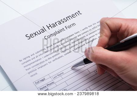 Close-up Of A Human Hand Filling Sexual Harassment Complaint Form With Pen