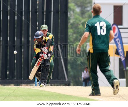 PUCHONG, MALAYSIA - SEPT 24: Malaysia's Ahmad Faiz bats Guernsey's Tim Ravenscroft's (13) bowl in this Pepsi ICC WCL Div 6 finals at the Kinrara Oval on September 24, 2011 in Puchong, Malaysia.