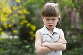 Pretty funny moody little blond preschool girl in white sleeveless dress looks into camera feeling angry and unsatisfied on blurred summer background. Children tantrum concept. poster