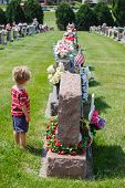 Young child standing in front of a headstone at a cemetery poster