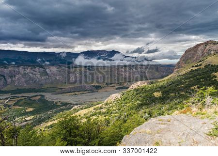 View at river Rio de las Vueltas in the valley under cloudy Andes mountains near Chalten town in Argentina