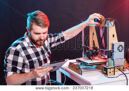 Young Male Designer Engineer Using A 3d Printer In The Laboratory And Studying A Product Prototype,