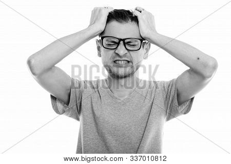 Studio Shot Of Angry Young Man Wearing Eyeglasses While Pulling His Hair