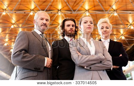 Group of Caucasian business women and men looking intimidating and professional in front of a gold back drop at a conference at a business event