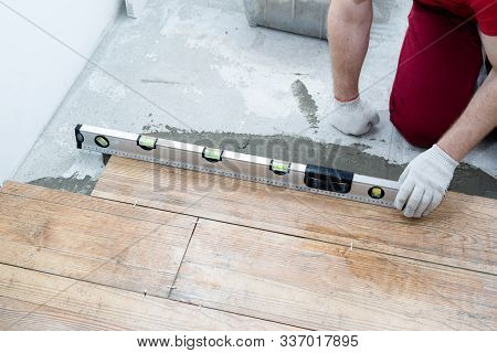 Repair And Decoration. The Tiler Puts The Porcelain Tiles On The Floor In The Apartment