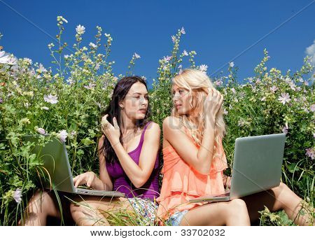 Two beautiful girl on laptop computer outdoors. Sit on green grass.