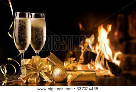 Celebration toast with champagne. Two champagne flutes with gold gift boxes and streamers in front of fireplace