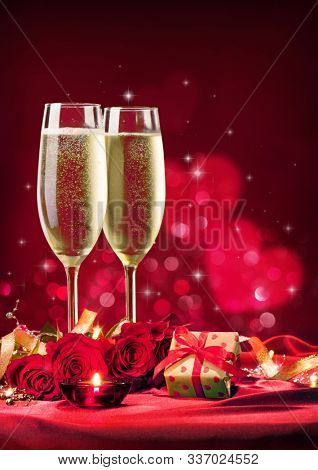Valentines day background with champagne glasses, red roses, gift box and candlelight