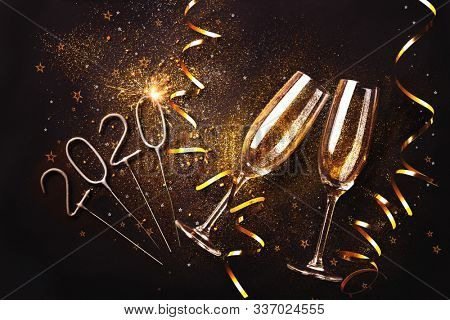 Celebration toast with champagne. Two champagne flutes with golden streamers on dark background