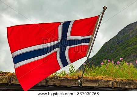 Sod Roof Hause And Norwegian Flag Waving Outdoor On Green Nature, Mountains In The Background