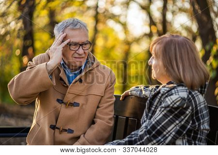 Senior Couple Is Sitting On Bench In Park And Talking About Their Health Problems.