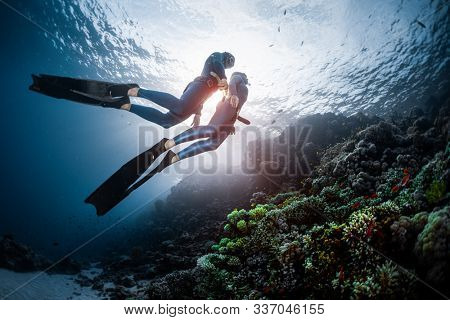 Two freedivers swim over the vivid coral reef in a tropical sea during their recreational freedive session