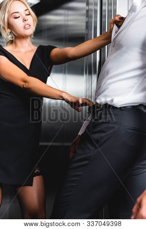 Woman Pulling By Waistband And Shirt Man In Office Elevator