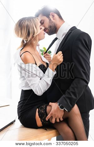 Business Couple Kissing While Flirting On Office Table