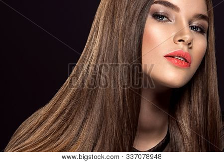 Woman with beauty long brown hair. Beautiful fashion model with long straight hair. Model with a smokey makeup. Pretty woman with orange color lipstick on lips. Pantone 2019.