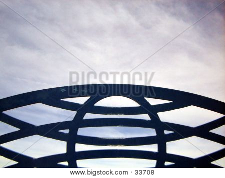 curved metal bench back against the sky poster