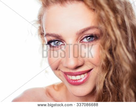 Portrait of a young beautiful girl with curly hair. Emotional cheerful woman on a white background
