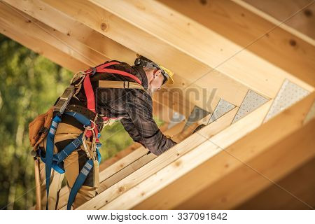 Wooden Roof Frame Construction Work. Caucasian Worker Finishing Wooden Skeleton Frame.construction I