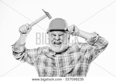 Home Improvement Repair. Man Bearded Laborer Wear Helmet Hold Hammer. Repair Workshop. Repair Concep
