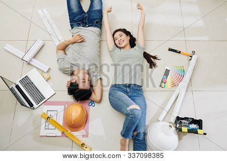 Happy Satisfied Young Vietnamese Couple Resting On The Floor After Planning Home Renovation, View Fr
