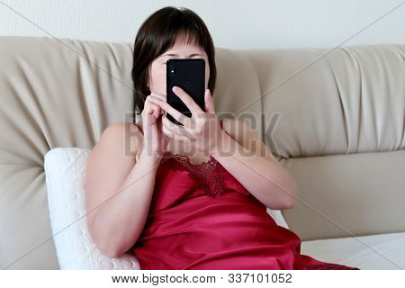 Woman Using Smartphone In Bedroom, Home Leisure. Hot Girl Wearing Red Negligee Laying On A Bed With