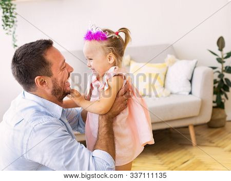 Family Time. Smiling Father Babysitting His Daughter In Pink Crown. Free Space, Selective Focus