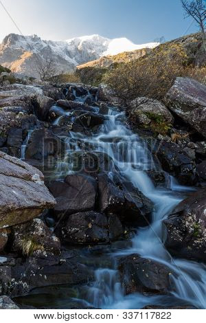 Early Morning Light And Shadow Over Mountains And Snow. Glyder Farw. Waterfall On Stream. Landscape