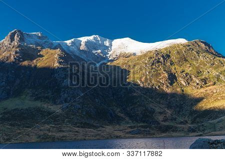 Early Morning Light And Shadow Over Mountains And Snow. Snow Capped Mountains, Y Garn, Lake Or Llyn