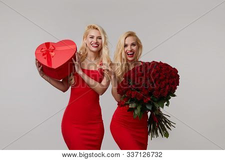 Two Happy Young Twin Women With A Big Bouquet Of Red Roses And A Red Heart Shaped Box. The Girl Was