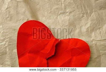 Broken red paper heart on crumpled paper background. Copy space for text