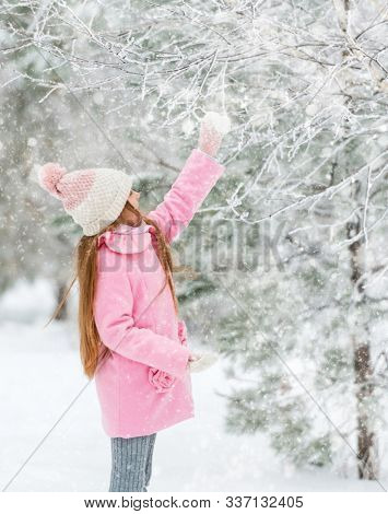 Warm-dressed child in the winter woods, touching the snow-covered tree, sideview