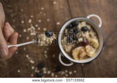 Woman's Hand And Porridge On A Spoon With Oat Flakes, Blueberries And Maple Syrup. Horizontal. Top V