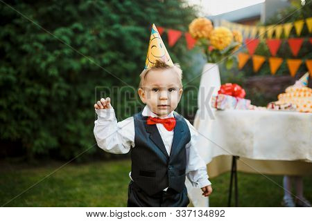 Table Set For Kids Birthday Party Outdoors In Garden And Cute Boy On Birthday Party. Happy Children