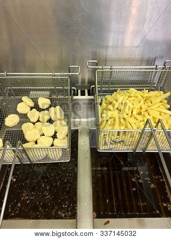 French Fries And Chicken Nuggets. Fried Food Ready For Cooking In A Deep Fryer