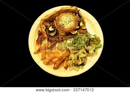 A Down View Of A Plate Of Flan, Chips And Salad Isolated Against A Black Background